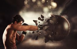Power and determination of a young muscular boxer against a wrecking ball. Self confident man destroys a wrecking ball royalty free stock photography