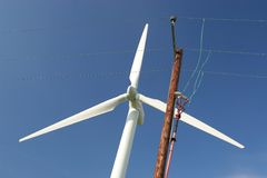 Power & Distribution. Electricity distribution lines with wind turbine behind stock image