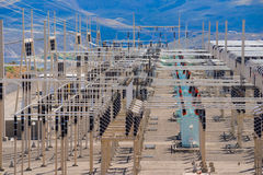 Power distribution substation. High voltage power distribution substation overlooking river canyon stock photo