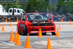 Power drift of race car between traffic cones. Cool power drift of a red race car going sideways between a lot of orange traffic cones Royalty Free Stock Photography