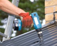 Power drill. Working with a Power drill on a roof Stock Photo