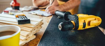 Power drill and Man making draft plan in the background Royalty Free Stock Images