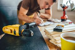 Power drill and Man making draft plan in the background Royalty Free Stock Photos