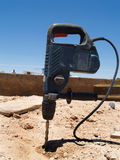 Power Drill Sticking into Ground - Vertical Stock Image