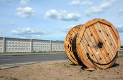 A power electric cable wound on a wooden coil against blue sky Royalty Free Stock Photo