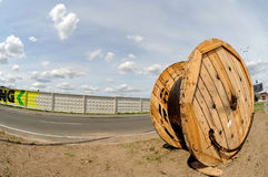 A power electric cable wound on a wooden coil against blue sky shot with a fisheye lens. Royalty Free Stock Photos
