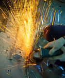 Power electric wheel grinding on part of car vehicle. Hand of worker working on electric wheel tool  grinding on part of car vehicle with fire sparking Royalty Free Stock Photos