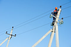 Power electrician lineman at work on pole. Electrician lineman repairman worker at climbing work on electric post power pole Royalty Free Stock Photos