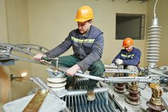Power electrician lineman at work. Electrician lineman repairman worker at huge power industrial transformer installation work Stock Images
