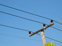 Power electricity lines installed on top of concrete pole. Three-phase power electricity lines installed on top of concrete pole with ceramic isolators blue sky Stock Photography