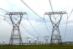 Power and Energy Pylons. Electricity pylons with energy and fuel production plant in the background Royalty Free Stock Image