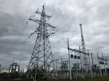 Power equipment of a power plant with a high-voltage line of wires and a transformer substation against a cloudy cloud background royalty free stock image
