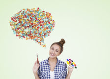 Power of expression. Girl with paintbrush and palette standing in light green background with speech bubble made of colorful icons. Concept of expressing oneself Royalty Free Stock Photos