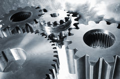 Power gear concept in blue. Large gear machinery reflecting in steel backdrop all in a metallic blue toning Stock Image