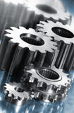 Power gears against blue steel Stock Photography