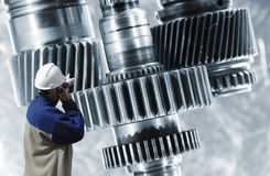 Power gears in titanium and steel. Engineer pointing at giant surreal gears and cogwheels assembly, titanium and steel Royalty Free Stock Images