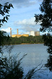 Power generating plant. A view across a small lake at a power plant and two tall cooling towers in the late afternoon Stock Image