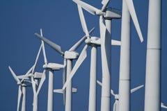 Power Generating Wind Turbines / Windmills. White, Electrical Power Generating Wind Turbines with blue sky background Stock Image