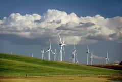 Power Generating Windmills. Stark White Electrical Power Generating Windmills on Rolling Hills, Beneath Dramatic Spring Cumulous Clouds, Rio Vista, California Stock Image