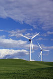 Power Generating Windmills. Stark White Electrical Power Generating Wind Turbines on Rolling Spring Wheat Covered Hills, Beneath Spring Clouds, Rio Vista Royalty Free Stock Photos