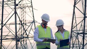 Power Generation concept. Professional electrical engineer working near high-voltage power line. 4K stock footage
