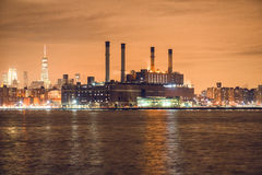 Power generation plant in New York City at night time on river bank Royalty Free Stock Image