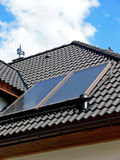 Power generator. Close up of the solar panels on the black tiled roof Stock Photos