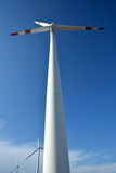 Power generators. Windmill power generator, under blue sky, shown as energy industry concept Stock Photo