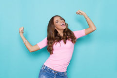 Power Girl In Pastel Colors. Happy beautiful young woman in pastel pink shirt shouting and flexing muscles. Waist up studio shot on turquoise background royalty free stock images