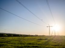 Power grid and electric wires in sunset. Electric power, grid and pillars on a field with the sun in background, at sunset Royalty Free Stock Photos