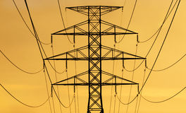Power Grid. Hydro power lines and tower silhouetted against the rising or setting sun royalty free stock photos