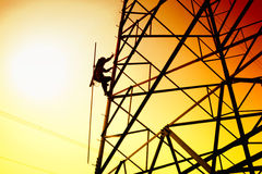 Power grid and worker. A worker climbing the power grid royalty free stock photography