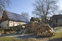 Power for the Home. A lot of alternative energies is putting on that yard. Solar panels and stack of logs are creating natural power Stock Image