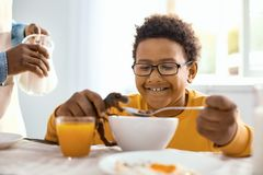 Cheerful pre-teen boy feeding toy dinosaur at breakfast. Power of imagination. Upbeat pre-teen boy feeding his toy dinosaur with cereals and smiling happily Royalty Free Stock Images