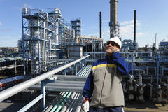 Power industries, oil and gas. Oil and gas installation with an oil worker talking in phone, pipelines and towers royalty free stock photo