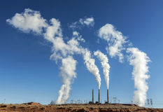 Power industry infrastructure. Chimney white smoke on a blue sky Royalty Free Stock Photos