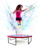 Power jump fitness. Fitness teacher jumps nimbly on the trampoline with colour light effect Royalty Free Stock Images
