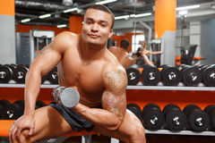Power lifter working out with dumbbells in gym Stock Images