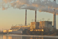 Power lights. Chimneys launching smoke. Cranes, extending the electron. Heat generation. United factory Stock Image