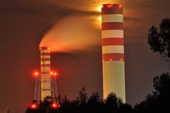 Power lights illuminated at night. Chimneys launching smoke. Cranes, extending the electron. Heat generation. United factory Royalty Free Stock Photos