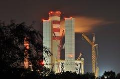 Power lights illuminated at night. Chimneys launching smoke. Stock Image