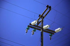 Power line. Polw with power and phone lines and junctions against a blue sky Royalty Free Stock Photography