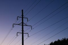 Power line against the evening sky. The power line with stretched wires clearly looms against the background of the evening sky Stock Image