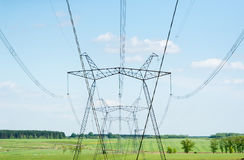 Power line against a green field. Royalty Free Stock Image