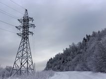 Power line along snow mountain road royalty free stock photos