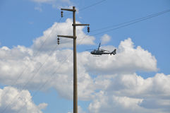 Power line, background helicopter flying Royalty Free Stock Photography
