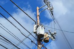 Power line cable and transformer - cloudy sky. Power line cable and transformer against hazy sky Royalty Free Stock Photos
