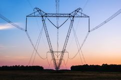 Power line in a field. On the background of beautiful sunset royalty free stock photography