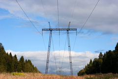Power line in the field under the blue sky Stock Images