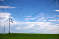Power line in the middle of a green field with blue sky Royalty Free Stock Photography